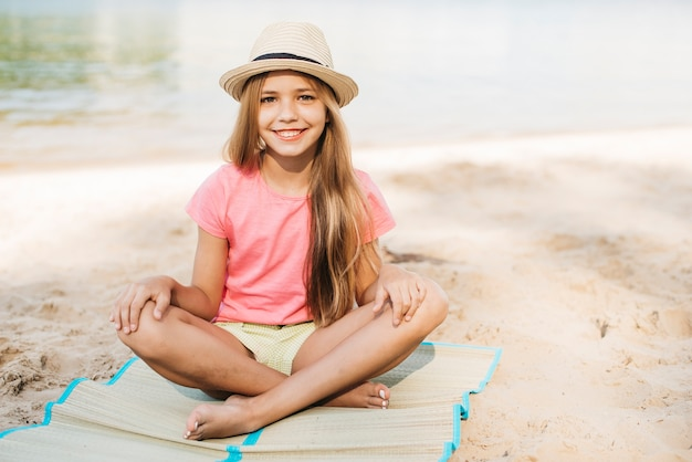 Smiling girl sitting at beach