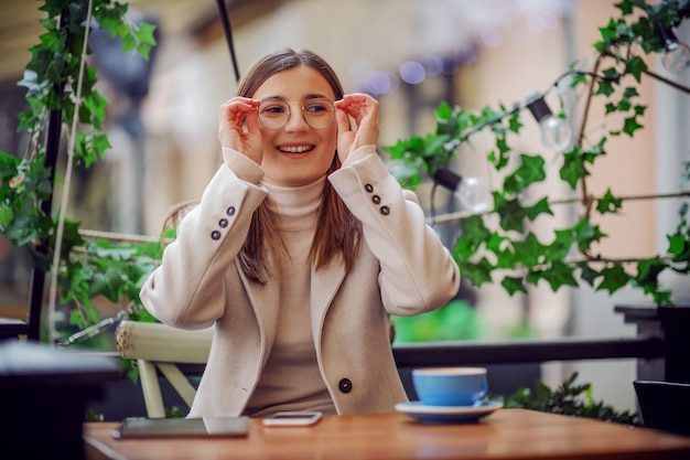 Smiling girl sitting in cafe and putting her glasses properly. she is having coffee break.