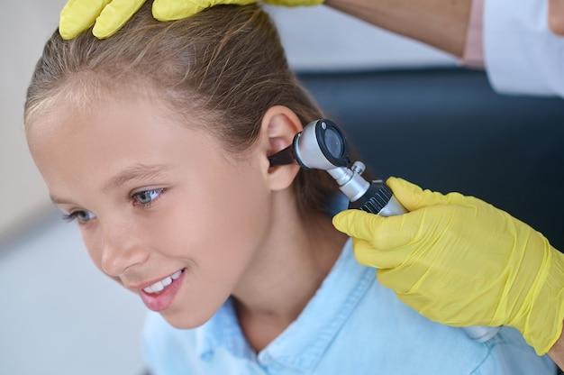 Smiling girl sitting calmly on examination of ear