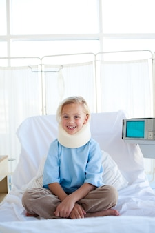 Smiling girl sitting on a hospital bed