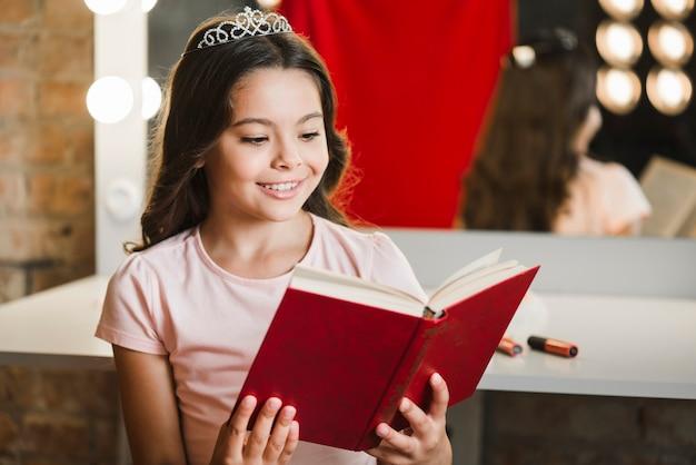 Smiling girl sitting at makeup room reading book