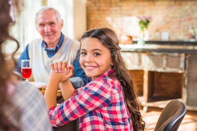 Smiling girl sitting near elderly man