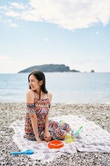 그녀의 머리를 옆으로 돌리는 자갈 해변에 담요에 앉아 웃는 소녀