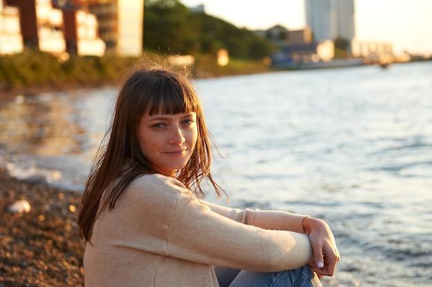 Улыбающаяся девушка сидит на пляже на закате