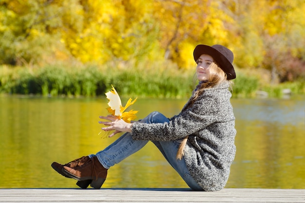 手に紅葉を持って桟橋に座っている笑顔の女の子。晴れた日