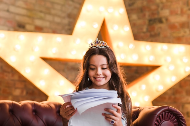 Smiling girl sitting on sofa reading scripts against glowing star in background