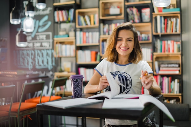Smiling girl sitting at table with notebooks