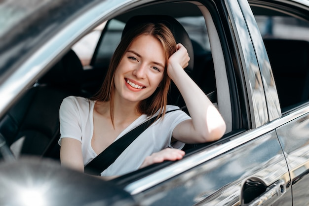 Smiling girl sitting behind the wheel of a car leaning head on hand .