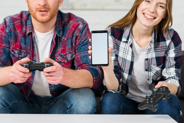 Smiling girl sitting with her boyfriend playing video game showing mobile screen display