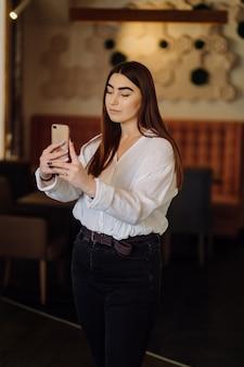 디지털 가제트를 사용하여 거리 카페에서 시간을 보내는 웃는 소녀