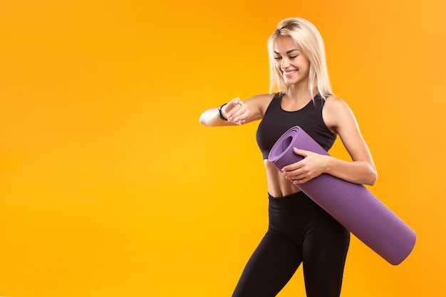Smiling girl in sportswear with a smart watch and a mat in her hands on a yellow background