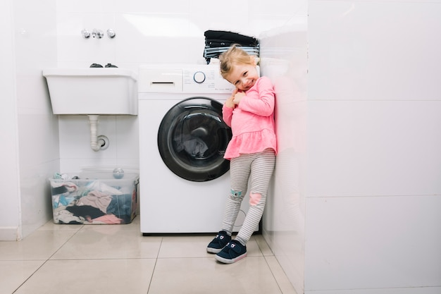 Smiling girl standing in front of washing machine