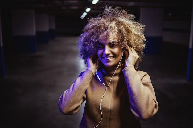 지하 차고에 서서 음악을 듣기 위해 이어폰을 씌우고 웃는 소녀.