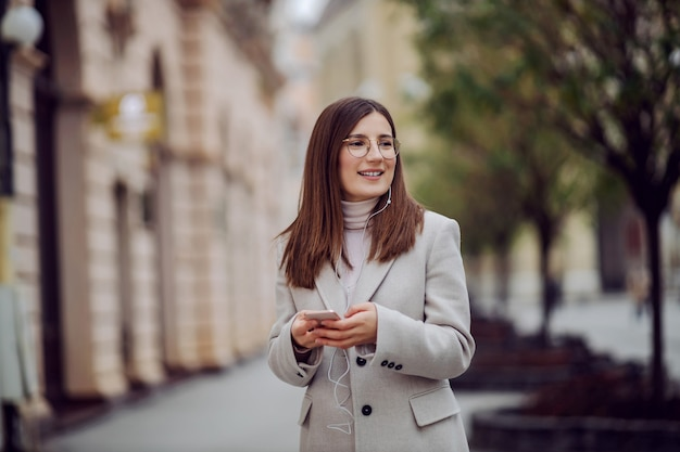 通りに立って、ビデオ通話で友達を呼んでいる笑顔の女の子。ミレニアル世代。