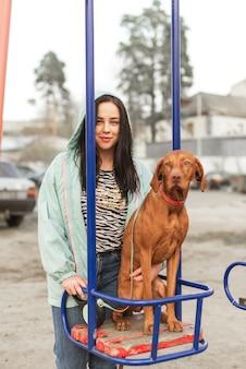 Улыбающаяся девушка стоит на улице с собакой на качелях