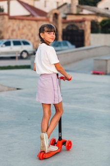 Smiling girl standing on push scooter looking back
