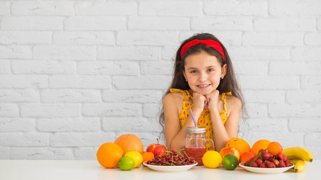 Smiling girl standing behind the white desk with colorful fresh organic ripe fruits