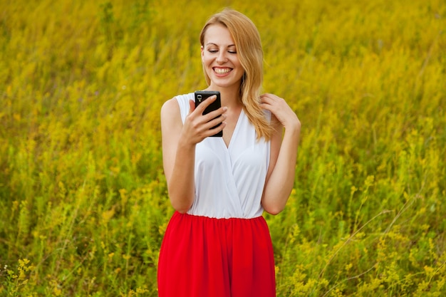 Smiling girl stands in a field of yellow flowers and poses in front of a photo camera