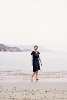 웃는 소녀는 산의 배경에 대해 바다로 모래 해변에 서