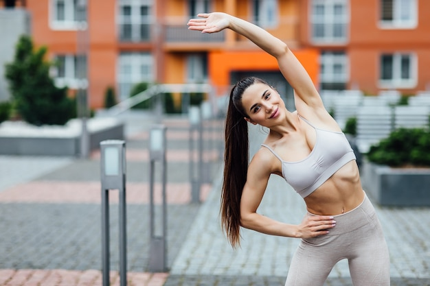 Smiling girl stretching after exercise outdoors on city street.