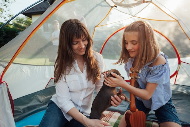 Smiling girl stroking little dog holding by her mother sitting in tent