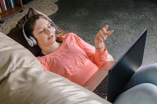 笑顔の女子学生がワイヤレスヘッドフォンを着用して通信またはオンラインで勉強