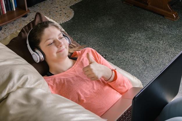 웃는 여자 학생 착용 무선 헤드폰 통신 또는 온라인 공부