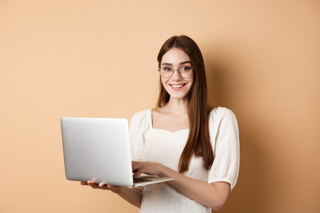노트북에서 작업, 안경을 착용 하 고 행복을 찾고 웃는 여자 학생 베이지 색에 서있는 동안 컴퓨터를 사용 하여.