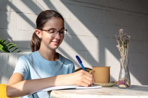 웃고 있는 여학생은 카페의 공책에 펜으로 숙제를 씁니다. 안경을 쓰고 대각선 그림자가 있는 카페에서 파란색 블라우스를 입은 백인 갈색 머리 소녀의 초상화. 학교 개념으로 돌아가기.