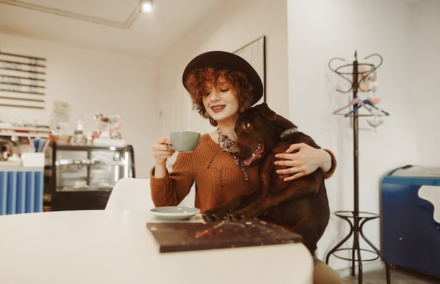 Smiling girl in stylish clothes and hat spends time in cafe with dog