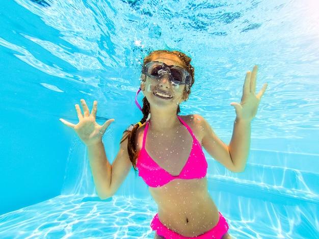 Smiling girl swimming underwater in pool