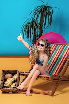 Smiling girl in swimsuit and sunglasses lying in rainbow deck chair with crossed legs and sunbathing