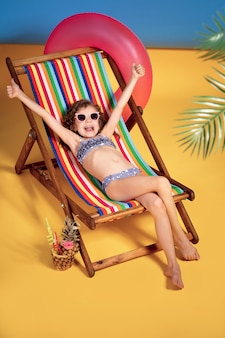 Smiling girl in swimsuit and sunglasses lying in rainbow deck chair with hands raised up emotionally and sunbathing