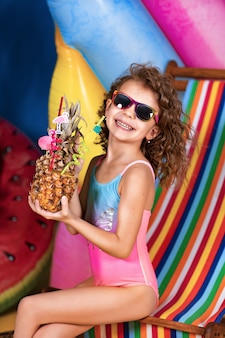 Smiling girl in swimsuit and sunglasses sitting in rainbow deck chair holding pineapple cocktail with colorful straws and showing thumb up and sunbathing