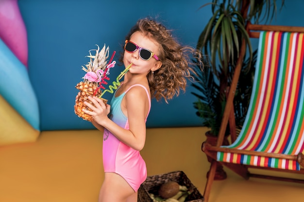 Smiling girl in swimsuit and sunglasses stay near rainbow deck chair holding pineapple with cocktail, colorful straws in it and sunbathing
