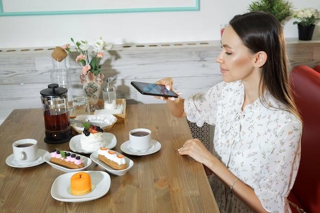 웃는 소녀는 카페 테이블에서 케이크와 차 사진을 찍는다