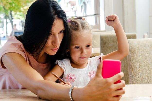 A smiling girl takes a selfie with a cute girl on a smartphone