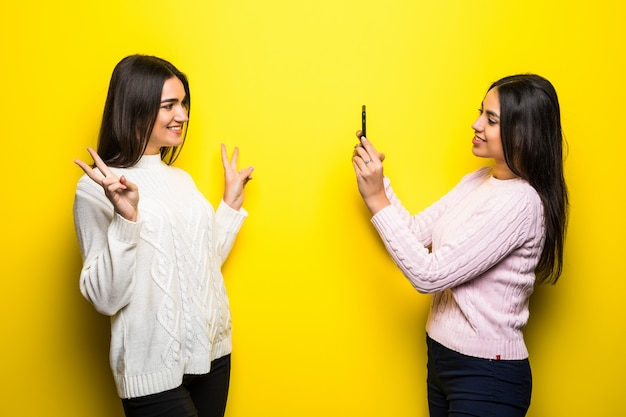 Smiling girl taking a photo of her girlfriend isolated over yellow wall