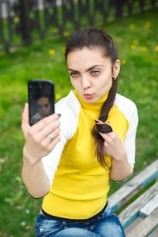 屋外でスマートフォンのカメラで写真を撮る笑顔の女の子。自撮り