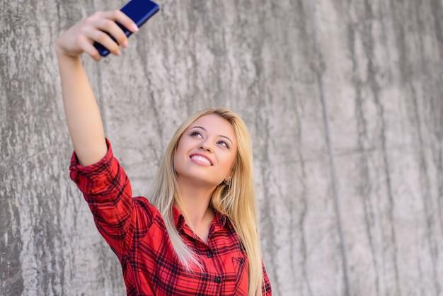 スマートフォンで自画像を撮る笑顔の女の子