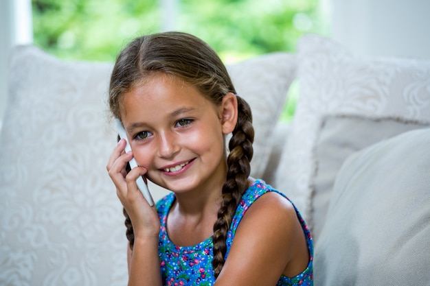 Smiling girl talking on mobile phone at home