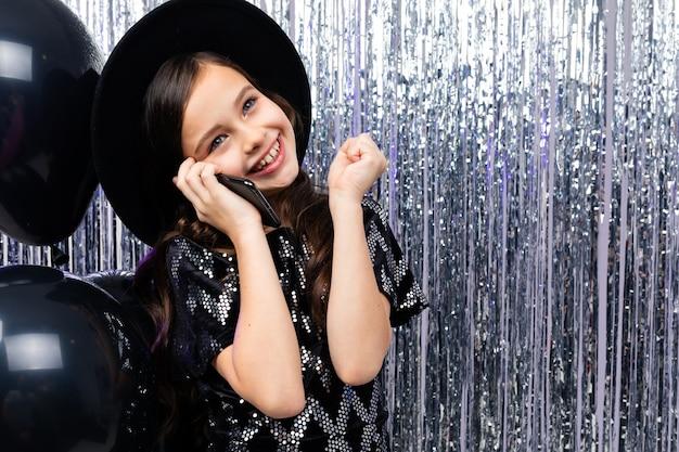 Улыбающаяся девушка разговаривает по телефону на вечеринке среди черных гелиевых шаров и мишуры