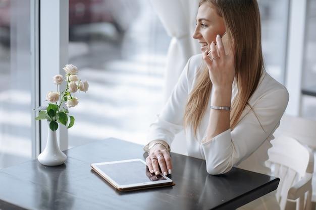 웃는 여자는 테이블에 태블릿 전화 통화