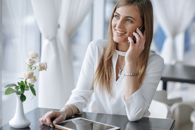 Smiling girl talking on the phone and touching the screen of a tablet