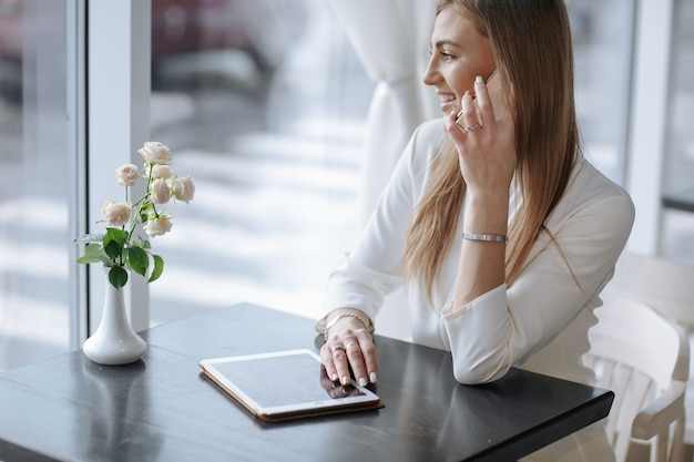 Smiling girl talking on the phone with a tablet on the table