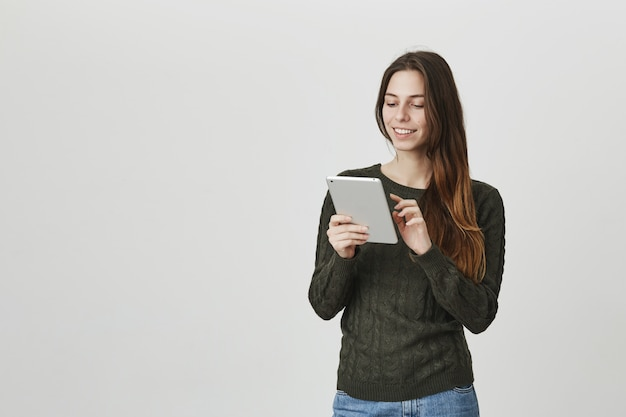 Smiling girl using digital tablet, edit picture in app