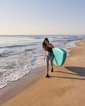 Улыбающаяся девушка гуляет по береговой линии с доской с веслом
