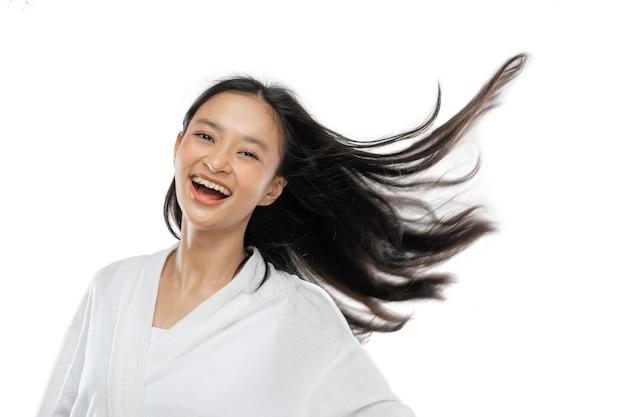 Улыбающаяся девушка в полотенце стоит с длинными волосами, развеваемыми ветром
