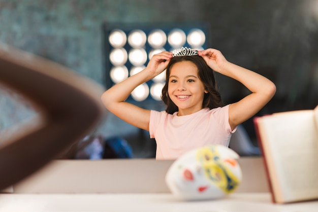 Smiling girl wearing diamond crown at backstage