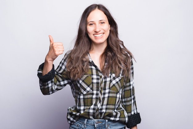 Smiling girl wearing green shirt is showing thumb up on white